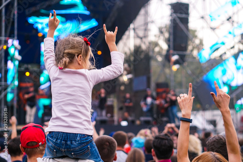 Fototapeta  Child has fun on her parents' shoulders keeping hands with them at an outdoor ro