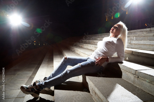 Ugly woman on the steps of stair in the city at night with lighting flashes in the black background