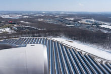 View Of Beautiful Solar Cell Farm Covered By Snow From A Airplane Window.