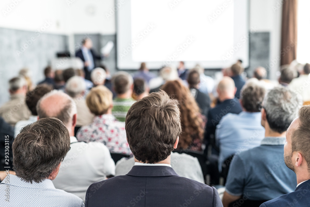 Fototapeta Speaker giving a talk in conference hall at business event. Audience at the conference hall. Business and Entrepreneurship concept. Focus on unrecognizable people in audience.