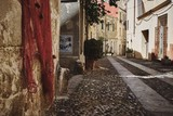 Fototapeta Uliczki - Old colorful neighborhood with a narrow street during daytime in Alghero Old town, Italy