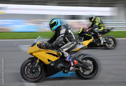 Vászonkép  Motorcycle racers compete on the race track