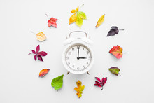 Colorful Different Autumn Leaves Around White Alarm Clock On Light Gray Background. Time Change Concept.
