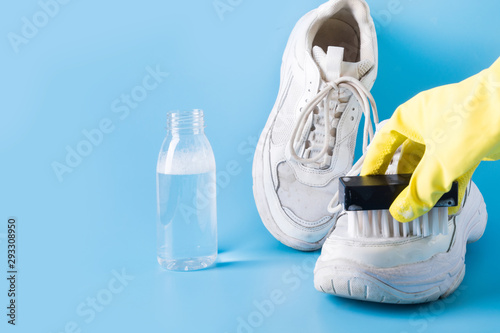 Dirty white sneakers with special tool for cleaning them on blue. Fototapeta