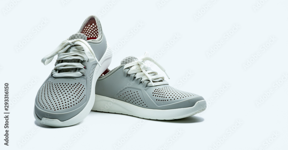 Fototapeta A pair of grey shoes on white background. Comfortable shoes with pore. Breathable rubber shoes. Footwear.