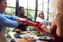 Group Of Friends Sitting Around Table At Home For Christmas Dinner Pulling Crackers