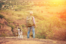 Tourist Man With A Gray Beard With His Dog Breed Of Husky Against The Backdrop Of Trees, Gorges And Stones, Concept Of Tourism And Outdoor Activities In Old Age With Animals