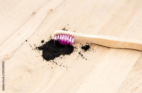 Raw activated charcoal powder on wooden background natural bamboo toothbrush inside it Canvas Print