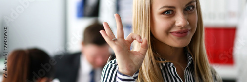 Photo Smiling female clerk showing OK or confirm sign with her arm close-up