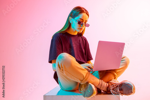 Modern Girl with laptop, tablet computer. Free creativity. A young blogger makes a Home office. Colored Neon light and background. - 293322752