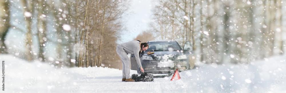 Fototapeta A man near a broken car on a winter day