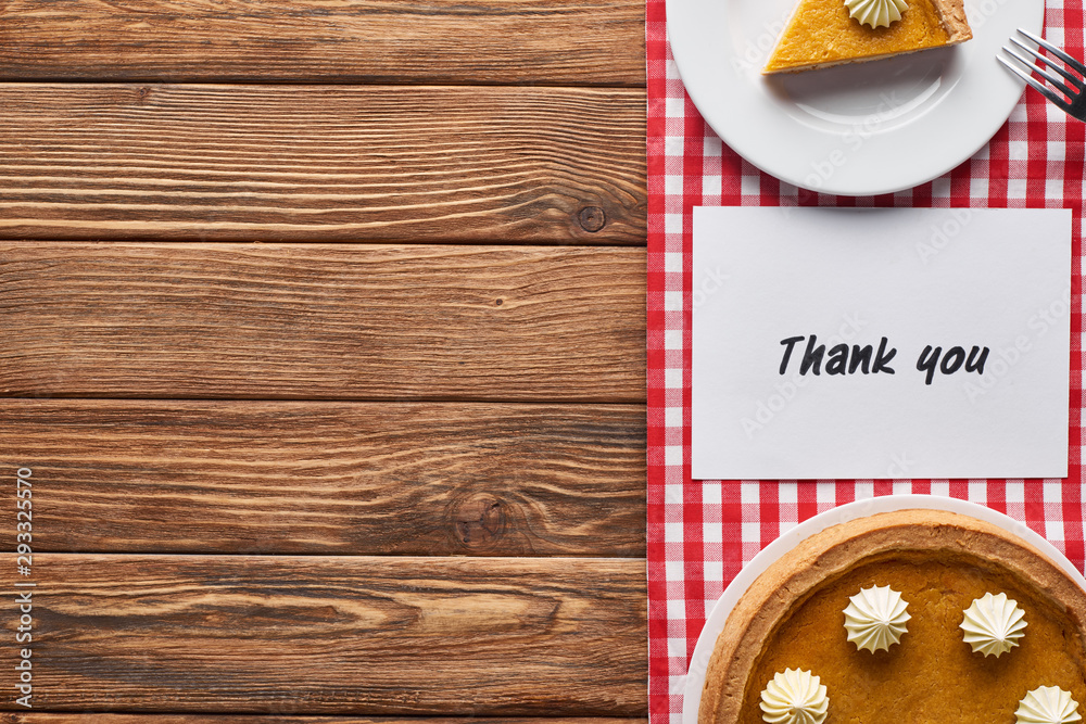 Fototapety, obrazy: top view of pumpkin pie and thank you card on wooden brown table with red plaid napkin