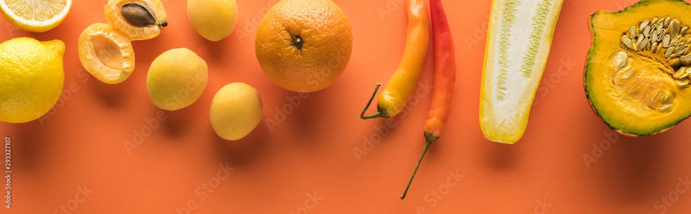 top view of yellow fruits and vegetables on orange background, panoramic shot