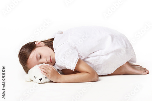 A little girl in a white dress, sleeps a cripple with a favorite toy against a white background Tapéta, Fotótapéta