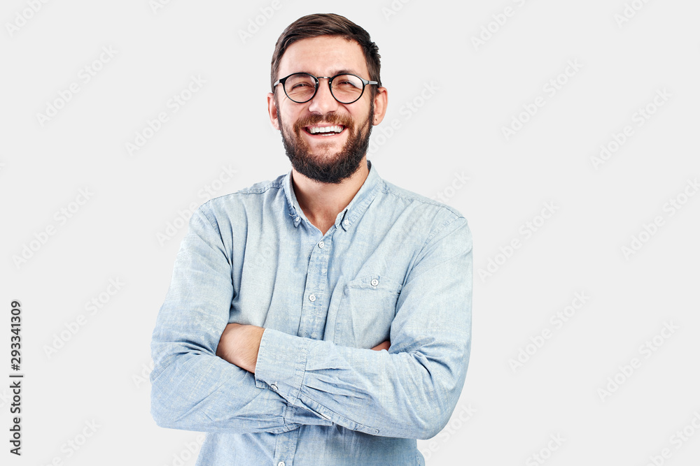 Fototapeta Friendly face portrait of an authentic caucasian bearded man with glasses of toothy smiling dressed casual against a white wall isolated