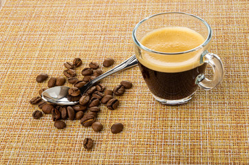 Spoon on coffee beans, cup with coffee espresso on mat