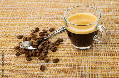 obraz lub plakat Spoon on coffee beans, cup with coffee espresso on mat