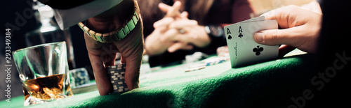 panoramic shot of man touching playing cards and poker chips near player Obraz na płótnie