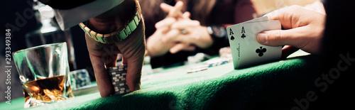 Valokuvatapetti panoramic shot of man touching playing cards and poker chips near player