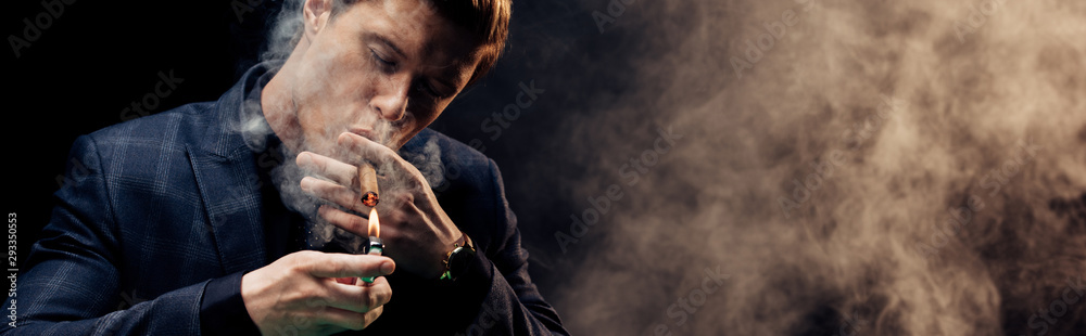Fototapety, obrazy: panoramic shot of handsome man holding lighter while smoking on black with smoke