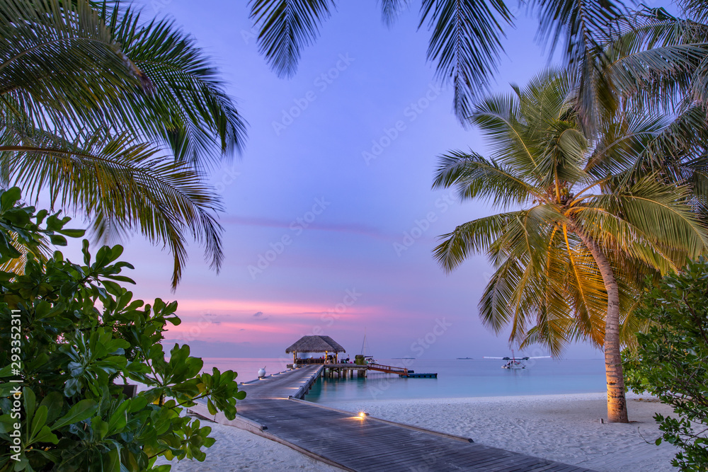 Fototapety, obrazy: Maldives resort island in sunset with wooden jetty, amazing colorful sky. Perfect sunset beach scenery. Detail of palm leaves on foreground. Vacation and beach relaxation, summer holidays background