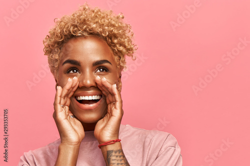 Fototapeta Horizontal of close up photo amazing beautiful dark-skinned lady draws attention to great cool event, concert, sale, discount message. Her arms hands help yell novelty, isolated pink background obraz