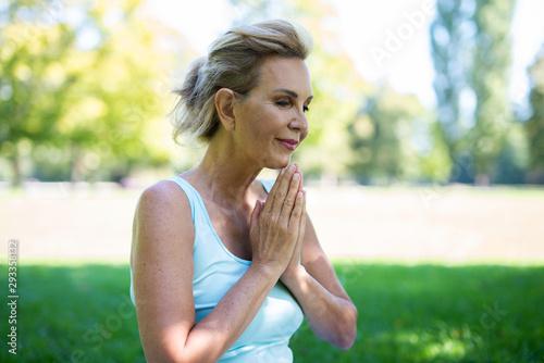Fototapeta Frau im mittleren Alter meditiert im Park