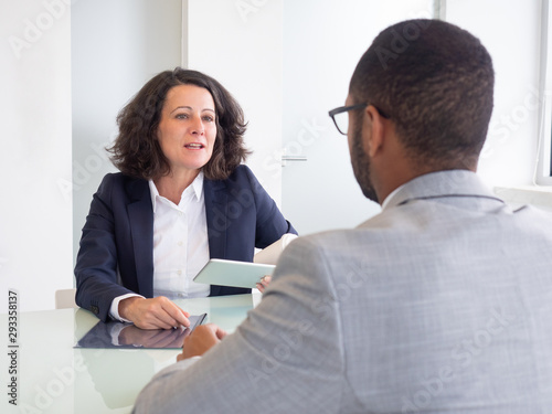 Business colleagues discussing project. Professional multiethnic businessman and businesswoman sitting at table and looking at each other in office. Cooperation concept