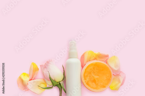 Poster Spa Open jar of cosmetic cream, white cosmetics bottle, rose and rose petals on pink background. Concept of natural spa cosmetics. Flat lay, top view, copy space.