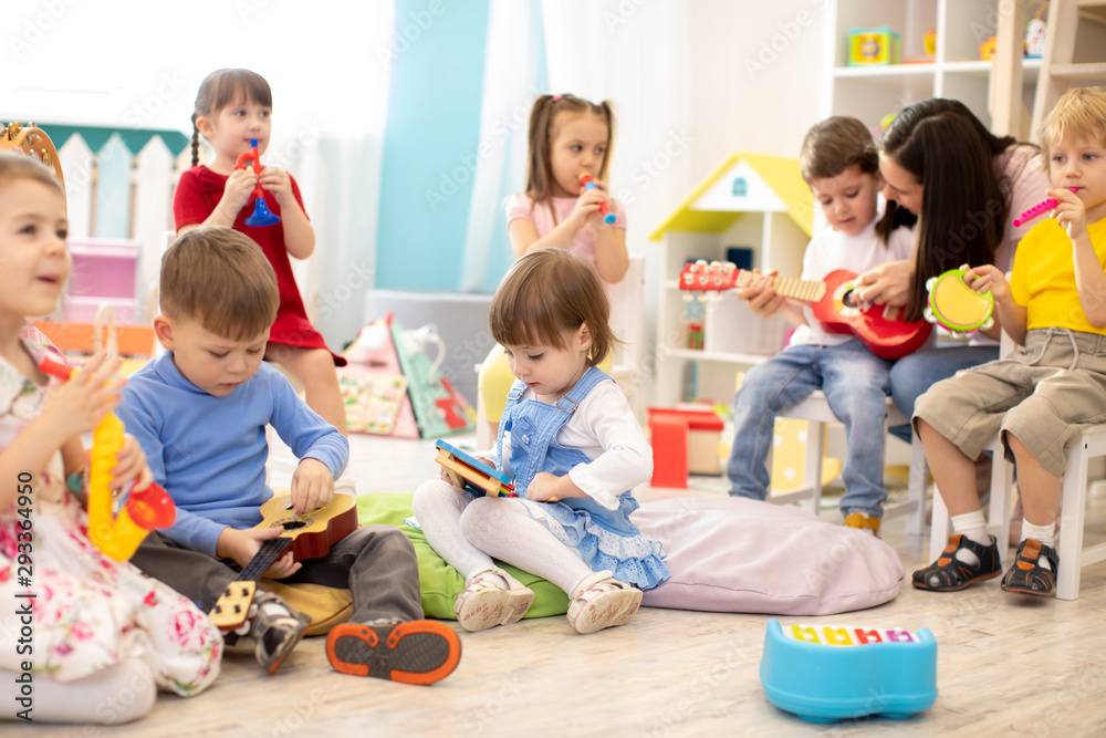 Fototapety, obrazy: Kindergarten teacher with children on music lesson in day care. Little kids toddlers play together with developmental toys.