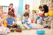 canvas print picture - Kindergarten teacher with children on music lesson in day care. Little kids toddlers play together with developmental toys.