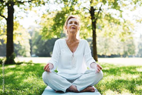 Photo Positive Frau im mittleren Alter macht Meditationsübungen im Park