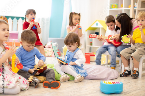 Kindergarten teacher with children on music lesson in day care. Little kids toddlers play together with developmental toys. - 293364950