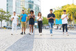 canvas print picture - Multiethnic friends walking together and texting messages on smartphones outside. Diverse men and women going down city street and using mobile phones. Communication concept