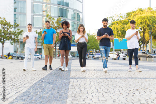 obraz PCV Multiethnic friends walking together and texting messages on smartphones outside. Diverse men and women going down city street and using mobile phones. Communication concept