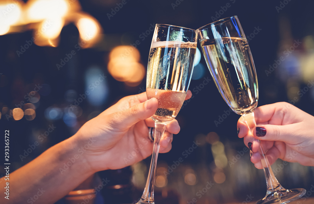 Fototapeta Two glasses with sparkling champagne wine in hands, concept for holiday, wedding valentines Christmas and New Year, bokeh, in a restaurant and cafe