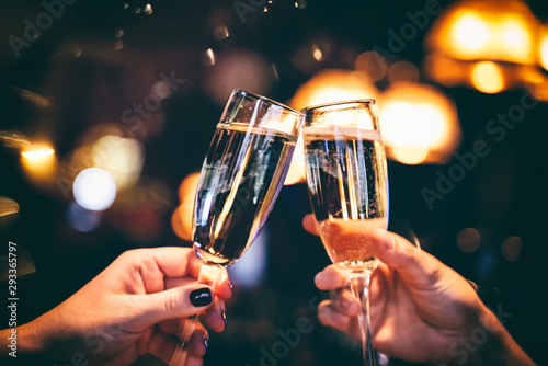 Fotografía  Two glasses with sparkling champagne wine in hands, concept for holiday, wedding