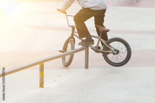 bmx rider in skate park practicing tricks sliding on frame of bike on ramp
