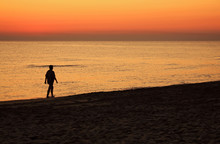 Walking At Dawn On The Beach