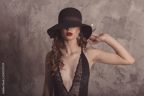 Foto auf Acrylglas Fashionable confident woman with red lips, female model posing in studio with beton background. Vintage plaid stockings, hat, glove. Girl hold glass for wine