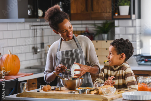 Fototapeta Son is helping mother to prepare pumpkin pie. American family. Single mother. Household chores for kids. obraz