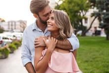 Loving Couple Walking By Street Outdoors Hugging