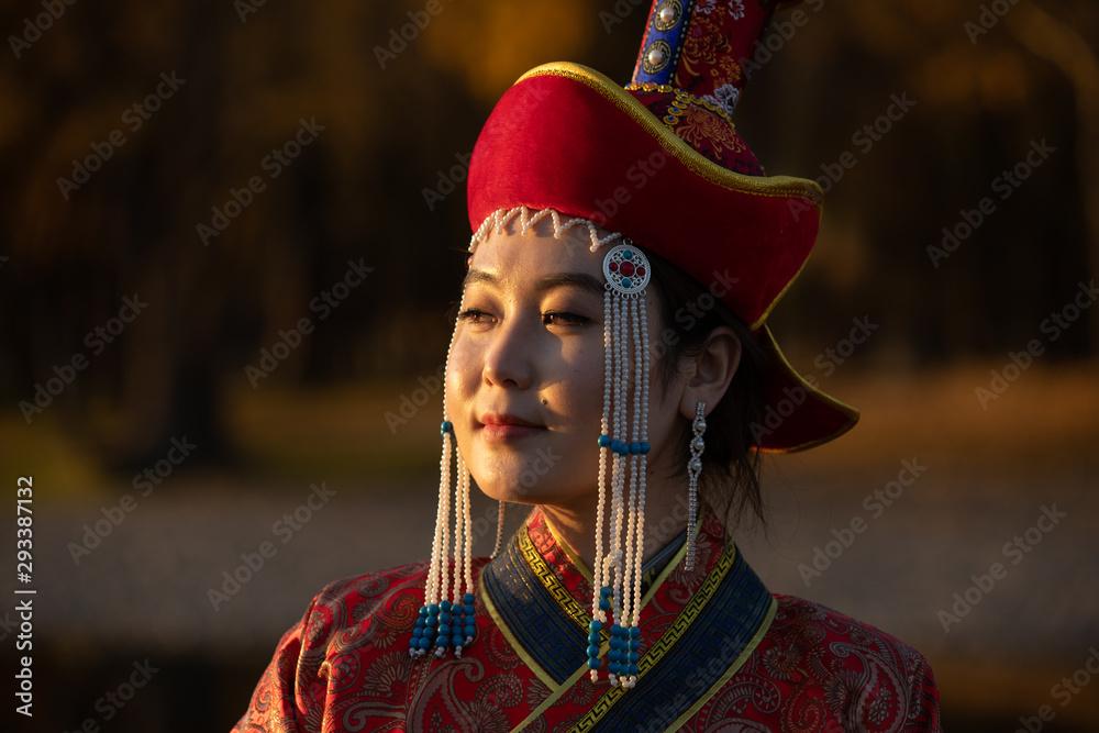 Fototapety, obrazy: Beautiful young woman posing in traditional Mongolian dress in sunset light. Ulaanbaatar, Mongolia.