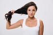 Leinwandbild Motiv smiling brunette beautiful woman holding long healthy and shiny hair isolated on grey