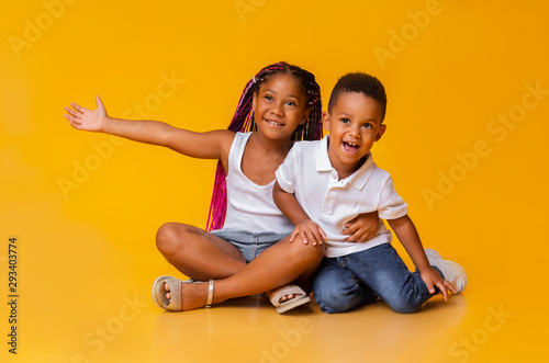 Fototapeta Adorable little sister and brother sitting on floor and cuddling