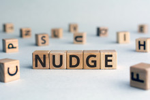 Nudge - Word From Wooden Blocks With Letters, Pushing Gently Concept, Random Letters Around, White  Background