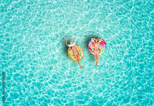 Valokuvatapetti Junges Paar genießt den Urlaub auf bunten Luftmatratzen über türkisem, tropische