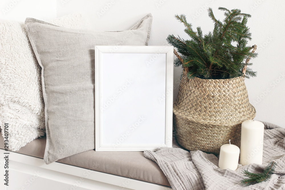 Fototapeta White blank wooden frame mockup with Christmas tree, candles, linen cushions and plaid on the white bench. Poster product design. Scandinavian home decor, nordic design. Winter festive concept.