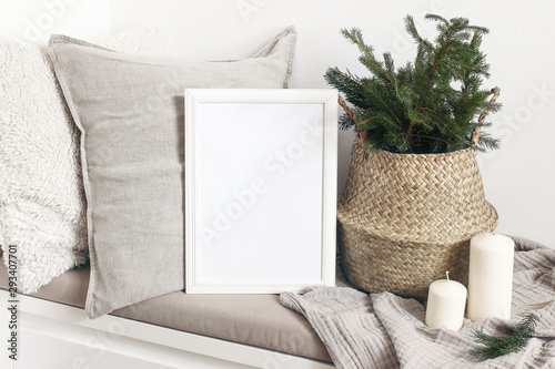 Stampa su Tela White blank wooden frame mockup with Christmas tree, candles, linen cushions and plaid on the white bench