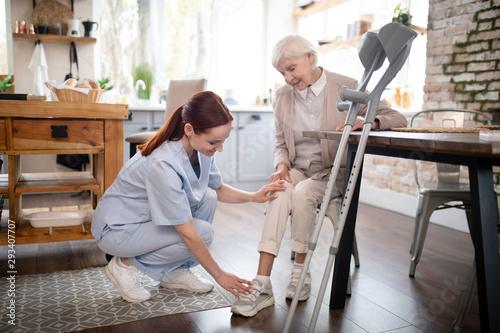 Photo Nurse wearing uniform taking care of aged woman
